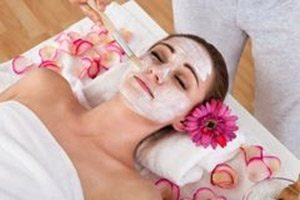 Facial treatment in progress with flower petals on treatment bed