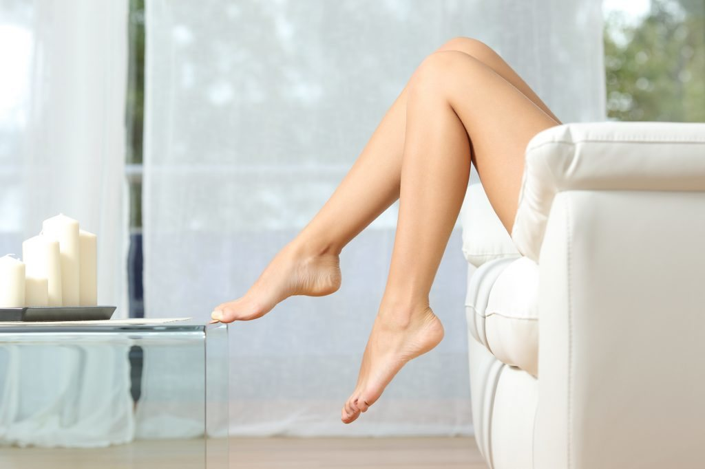 Woman's bare legs with toe on glass table show normal blood flow