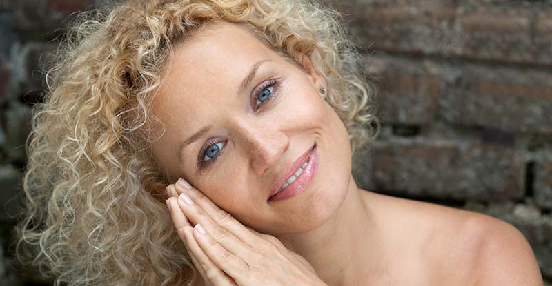 Curly-haired blonde woman with tilted head with a brick wall background