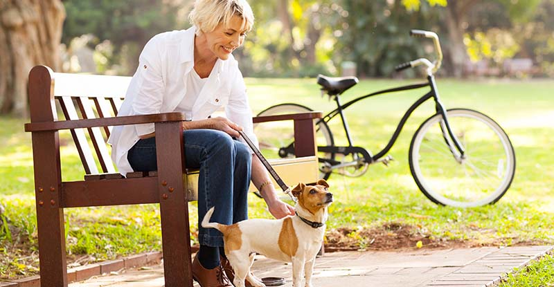 Older woman with her bike and dog on a park bench in Spring Grove, Illinois