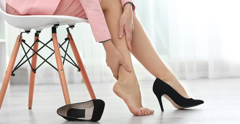 Woman in pink suit and black pumps sits in a chair while massaging her ankle