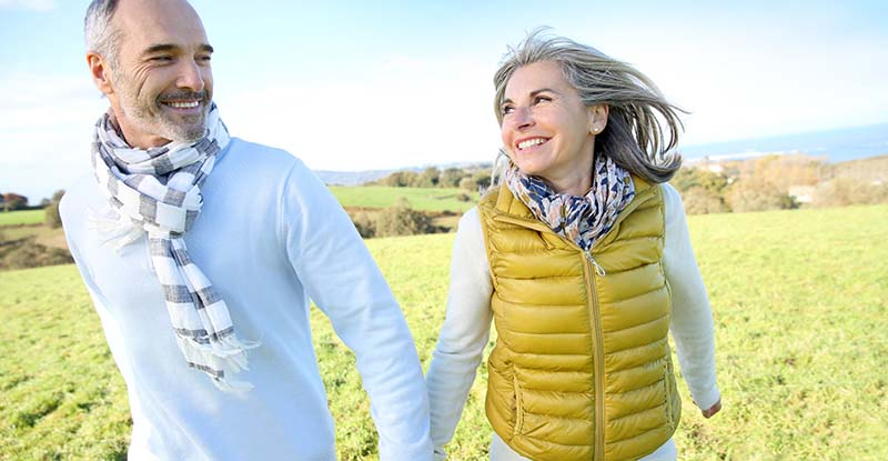 Older couple holding hands on a brisk day while hiking on a hill in Woodstock, Illinois