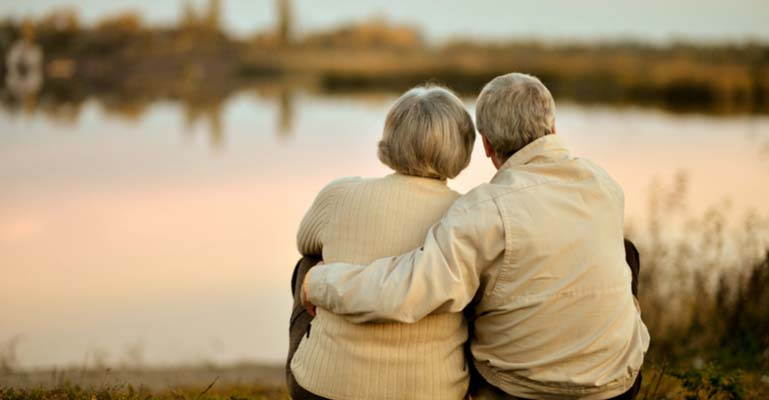 Elderly couple embracing while seated next to a lake at sunrise