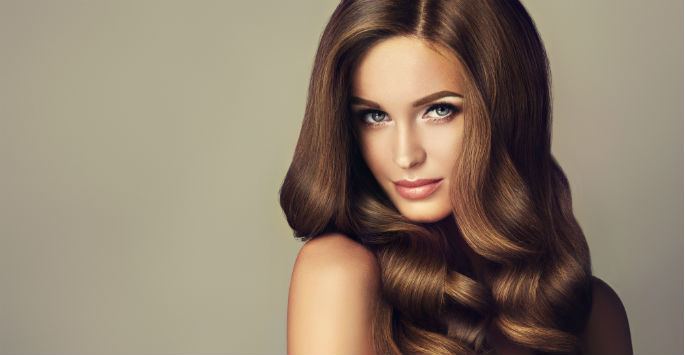 Stunning close up of a model with rich, long-flowing brown wavy hair