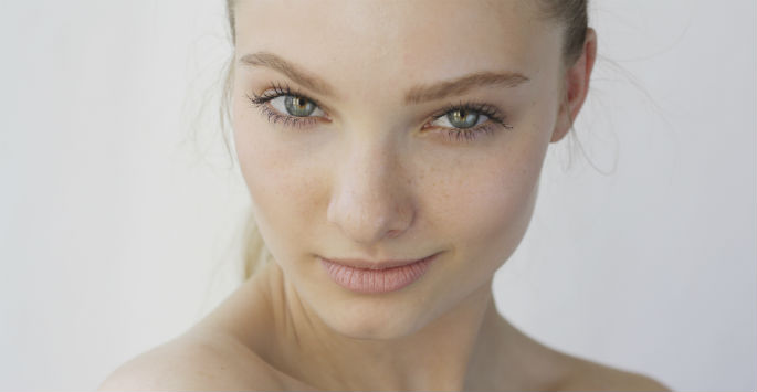 Youthful face of fair-skinned woman with green eyes