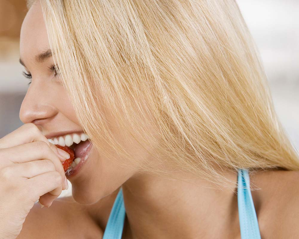 Close up of pretty blonde haired woman eating a strawberry