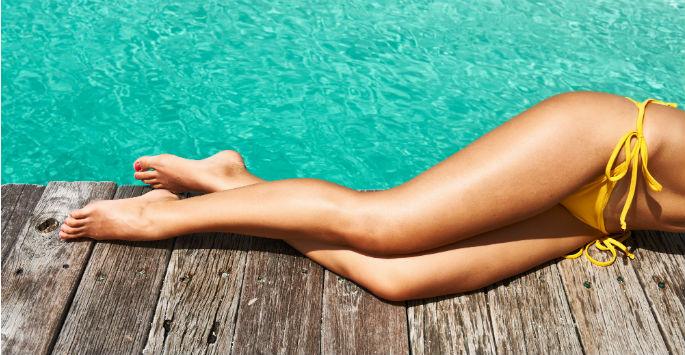 Beautiful smooth legs of woman in yellow bikini on pier next to the ocean