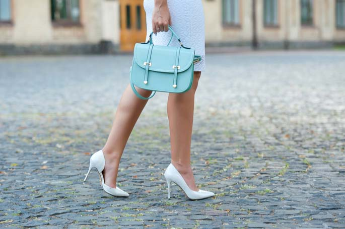 A pair of lady's legs in white high-heeled pumps on a cobblestone walk carrying a light blue purse