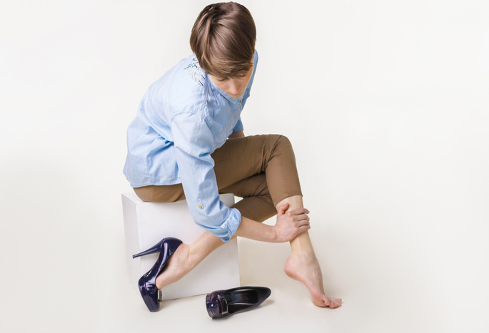 A short-haried lady in a blue oxford and navy pumps rubs her painful leg