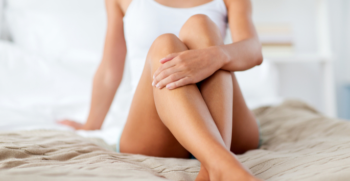 Female holding her tanned bare legs while relaxing in bed