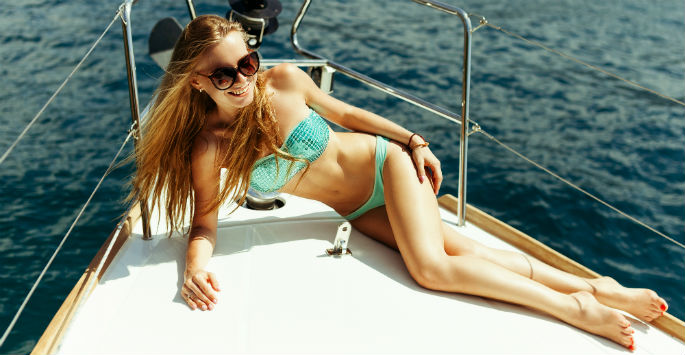 Bikini-clad woman in sunglasses poses on the front of a yacht
