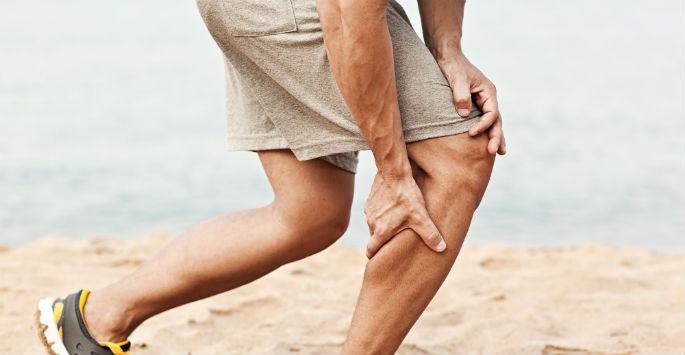A man in shorts grabbing is legs as he runs on the beach
