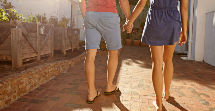 A couple in shorts holding hands walking on a brick-paved walkway