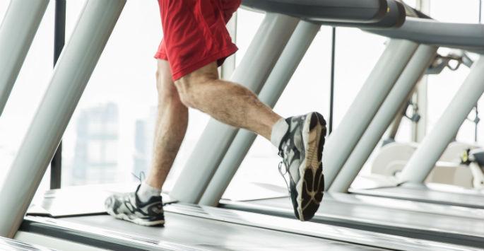 Man's legs running on treadmill overlooking a city view