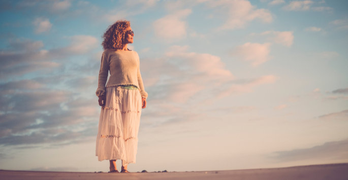 Curly-haired woman with sunglasses looks at sunset while on the beach with sky behind her