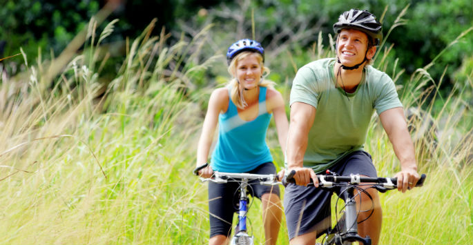 Active young couple biking outdoors helps keep veins healthy