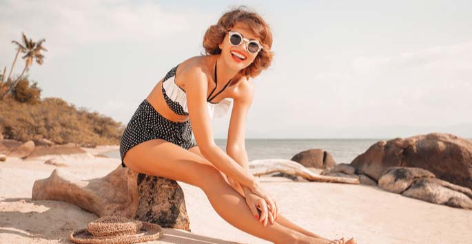 Lady in 1950s style bathsuit and white sunglasses sitting on a beach rock