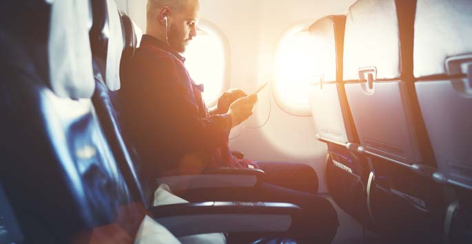 Man in airplane window seat checking his phone