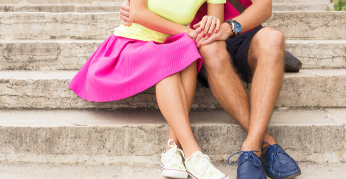 The bare legs of a couple sitting together on stone steps